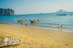 AO NANG, ΤΑΪΛΆΝΔΗ - 5 ΜΑΡΤΊΟΥ 2018: Μη αναγνωρισμένοι άνθρωποι που περπατούν στην παραλία κοντά στην αλιεία των ταϊλανδικών βαρκώ Στοκ Φωτογραφία