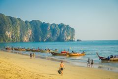 AO NANG, ΤΑΪΛΆΝΔΗ - 5 ΜΑΡΤΊΟΥ 2018: Μη αναγνωρισμένοι άνθρωποι που περπατούν στην παραλία κοντά στην αλιεία των ταϊλανδικών βαρκώ Στοκ εικόνες με δικαίωμα ελεύθερης χρήσης