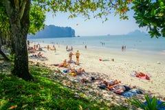 AO NANG, ТАИЛАНД - 19-ОЕ МАРТА 2018: Внешний взгляд неопознанных людей принимая солнце в песке на пляж Ao Nang с Стоковая Фотография RF