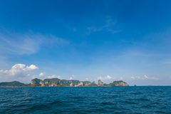 Ao Nang from the sea. Longtail boat on tropical Ao Nang beach  in Thailand. Landscape taken from the sea with blue sky and white sand Royalty Free Stock Image