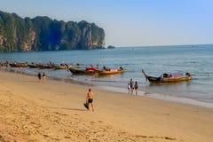 AO NANG TAJLANDIA, MARZEC, - 05, 2018: Plenerowy widok niezidentyfikowani ludzie chodzi w plaży blisko do Łowić tajlandzkie łodzi Zdjęcia Stock