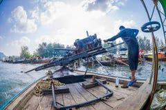 AO NANG, THAILAND - FEBRUARI 09, 2018: Oidentifierad man som behandlar en fartygmotor med en suddig naturbakgrund Arkivfoto