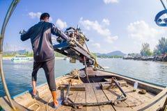 AO NANG, THAILAND - FEBRUARI 09, 2018: Oidentifierad man som behandlar en fartygmotor med en suddig naturbakgrund Royaltyfria Foton
