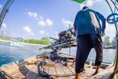 AO NANG, THAILAND - FEBRUARI 09, 2018: Oidentifierad man som behandlar en fartygmotor med en suddig naturbakgrund Arkivfoton