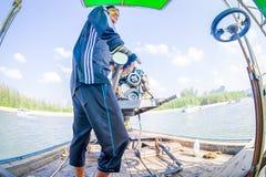 AO NANG, THAILAND - FEBRUARI 09, 2018: Slut upp av den oidentifierade mannen som behandlar en fartygmotor med en suddig natur Arkivbild