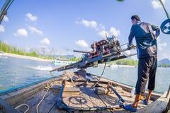 AO NANG, THAILAND - FEBRUARI 09, 2018: Slut upp av den oidentifierade mannen som behandlar en fartygmotor med en suddig natur Royaltyfria Bilder