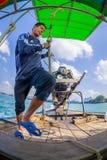 AO NANG, THAILAND - FEBRUARI 09, 2018: Utomhus- sikt av den oidentifierade mannen som behandlar en fartygmotor med en suddig natu Royaltyfri Fotografi