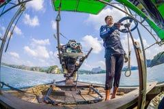 AO NANG, THAILAND - FEBRUARI 09, 2018: Utomhus- sikt av den oidentifierade mannen som behandlar en fartygmotor med en suddig natu Royaltyfria Foton