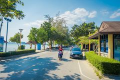 AO NANG, THAILAND - FEBRUARY 09, 2018: Outdoor view of some cars parked at one side of the road and unidentified woman. Riding a motorcycle close to local shops stock image