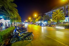 AO NANG, THAILAND - FEBRUARY 09, 2018: Outdoor view of some motorcycles parked in a row at one side close to many shops. In the street during night in AO Nang stock image