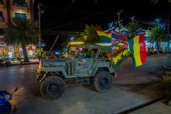 AO NANG, THAILAND - FEBRUARY 09, 2018: Outdoor view of unidentified man in his green car with many flags of Bob Marley. Close to many shops at Ao Nang street Stock Photography