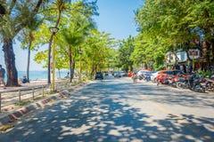 AO NANG, THAILAND - 19. MÄRZ 2018: Ansicht im Freien einiger Autos und Motorräder parkte in der Straße mit einige Palme Lizenzfreie Stockfotos