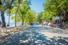 AO NANG, THAILAND - MARCH 19, 2018: Outdoor view of some cars and motorcycles parked in the street with some palms tree. Close to local shops at Ao Nang beach Royalty Free Stock Photos
