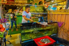 AO NANG, THAILAND - MARCH 05, 2018: Unidentified people inside of a restaurant, and a fish tak with lobsters ready to. Cook at Ao Nang town, in Thailand Royalty Free Stock Photography