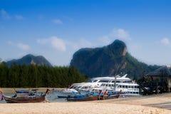 AO NANG, THAILAND - MARS 05, 2018: Utomhus- sikt av att fiska thai fartyg på kusten med enorma lyxiga fartyg med turister Royaltyfri Bild