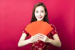 Año Nuevo chino feliz mujer joven con el sobre rojo Imagenes de archivo