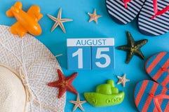 15 août Image de calendrier du 15 août avec les accessoires de plage d'été et l'équipement de voyageur sur le fond Arbre dans le  Image libre de droits