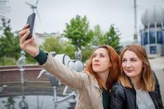 Aoman alegre dos que toma el selfie usando el teléfono móvil Fotografía de archivo