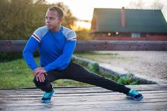 Aoutdoors τεντώματος αθλητών που κάνουν τις ασκήσεις που εξισώνουν στο ηλιοβασίλεμα Έννοιες ικανότητας Στοκ Φωτογραφία