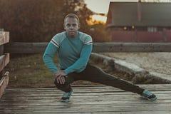 Aoutdoors τεντώματος αθλητών που κάνουν τις ασκήσεις που εξισώνουν στο ηλιοβασίλεμα Έννοιες ικανότητας Στοκ Εικόνες