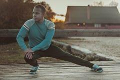 Aoutdoors τεντώματος αθλητών που κάνουν τις ασκήσεις που εξισώνουν στο ηλιοβασίλεμα Έννοιες ικανότητας Στοκ Εικόνα