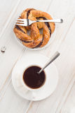 Aoverhead shoot of cup of black coffee with pastry loop on wood Stock Images