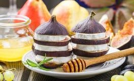 Apéritif des figues et du fromage de chèvre avec du miel Photographie stock