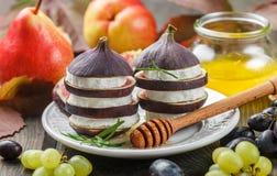 Apéritif des figues et du fromage de chèvre avec du miel Image stock