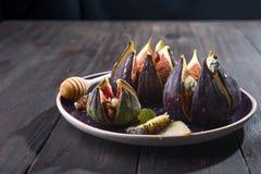 Apéritif gastronome des figues avec du fromage de chèvre, les noix et le miel du plat en céramique et du fond en bois brun, tradi photos stock