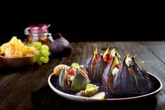 Apéritif gastronome des figues cuites au four avec du fromage de chèvre, les noix et le miel du plat en céramique et du fond en b photographie stock libre de droits