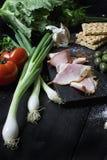 Apéritif réglé sur le conseil en bois Avec des olives, persil, tomate, ail Vue supérieure Fond foncé images stock