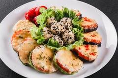 Apéritif sain, courgette grillée et aubergine avec du fromage avec du fromage du plat au-dessus du fond en pierre noir photographie stock