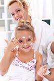 Após o cuidado do corpo do banho - aplicando o creme de face Imagem de Stock