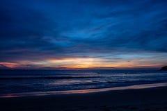 Após os grupos de Sun atrás do horizonte na praia de Karon foto de stock royalty free