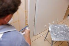 Após ter colocado as telhas na parede, você deve encher os espaços entre as telhas, uma massa especial do cimento ou a fuga foto de stock
