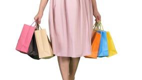 Ap?s sacos de compras levando da jovem mulher da compra do dia ao andar no fundo branco fotografia de stock royalty free