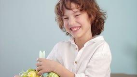 Ap van Klaus portret van een krullende roodharige jongen met een mand van paaseieren in zijn handen Gelukkige Pasen stock video