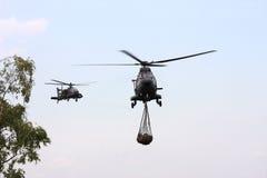 Apache militar está dirigiendo un heli del transporte del puma Imagenes de archivo