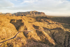 Apache trail - historical route at sunset lights,  Arizona. Overlooking view of Apache Trail scenic route near Phoenix, Arizona. Endless curving road running to Royalty Free Stock Photos