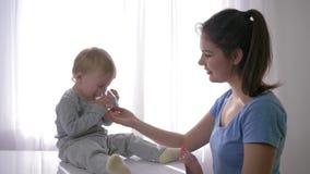 Apagando sed de poco niño, bebé gritador que bebe el agua pura del vidrio de las manos de la madre para apagar sed adentro metrajes