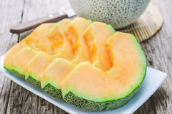 Apanese melons at white dish on wooden table Stock Photo