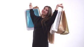 Aparência caucasiano da menina bonito que admira-se e suas compras, que realiza em suas mãos levantadas vídeos de arquivo