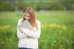 Aparência europeia da menina feliz que está na grama com um portátil no fundo verde da natureza Fotos de Stock