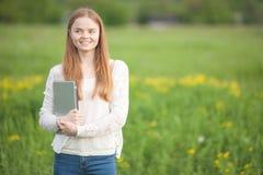 Aparência europeia da menina feliz que está na grama com um portátil no fundo verde da natureza Imagens de Stock