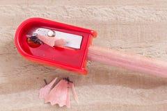 Apara-lápis vermelho e lápis isolados no backgro de madeira marrom Foto de Stock Royalty Free