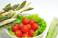 Aparagus And Tomatoes. Cherry tomatoes in a bowl with asparagus on the side Stock Images