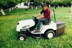 Aparamento de Gardner e jardim profissionais ajardinar usando um passeio no cortador de grama Imagens de Stock