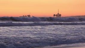 Aparejos costeros de la perforación petrolífera silueteados contra la puesta del sol del océano almacen de metraje de vídeo