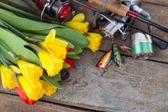 Aparejos de pesca con las flores de la primavera del ramo Imagen de archivo libre de regalías