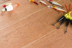 Aparejos de pesca del capítulo - giro, ganchos y señuelos de la pesca en fondo de madera ligero Visión superior Fotografía de archivo